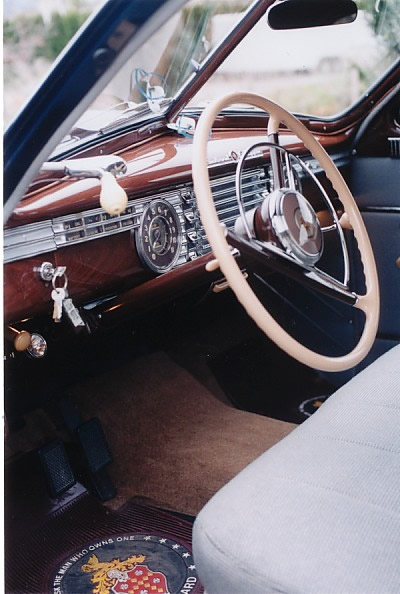The Interior: note the simulated wood grained dash, ignition key on the left of the steering wheel and the special floor mats with Packard crest and slogan 'Ask the man who owns one'